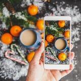 Boże Narodzenia i nowego roku ` s pojęcie Kobiet ręki fotografowali na smartphone nowego roku ` s skład mandarynka, świerkowy bra zdjęcia royalty free