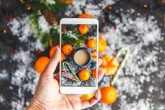 Boże Narodzenia i nowego roku ` s pojęcie Kobiet ręki fotografowali na smartphone nowego roku ` s skład mandarynka, świerkowy bra obraz royalty free