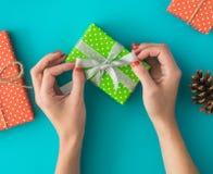 Boże Narodzenia i nowego roku wakacyjny skład z prezentów pudełkami, sosna rożek, kobiety ` s ręki pakują prezent na błękitnym tl Fotografia Royalty Free