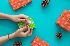 Boże Narodzenia i nowego roku wakacyjny skład z prezentów pudełkami, sosna rożek, kobiety ` s ręki pakują prezent na błękitnym tl Zdjęcia Royalty Free