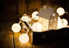 Boże Narodzenia i nowy rok bawełniana piłka zaświecają girlandę w rocznik drewnianej tacy i świeczka właścicielu w kształcie dom, Obraz Stock