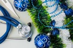 Boże Narodzenia i nowy rok dekoracje zbliżają sprzęt medycznego Medyczny stetoskop i termometr kłama blisko sztucznego śniegu z g Fotografia Stock