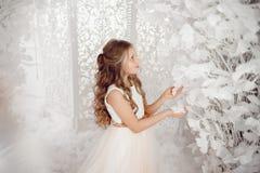 Boże Narodzenia i nowy rok, dziewczyna w biel sukni dotykają sztucznego drzewa zdjęcie stock