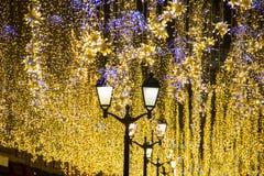 Boże Narodzenia i nowy rok wakacji iluminacja plenerowa w miasto ulicie przy nocą Złoty migocący obraz stock