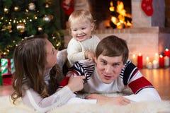 Boże Narodzenia, mas, rodzina, ludzie, szczęścia pojęcie - szczęśliwi rodzice bawić się z ładnym dzieckiem Obraz Stock
