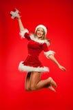 Boże Narodzenia, mas, zima, pojęcie - uśmiechnięta kobieta w Santa pomagiera kapeluszu z prezenta pudełkiem, szczęście skok dla r Fotografia Stock