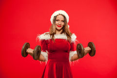 Boże Narodzenia, mas, zima, szczęścia pojęcie - Bodybuilding Silna dysponowana kobieta ćwiczy z dumbbells w Santa pomagierze Fotografia Royalty Free