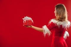 Boże Narodzenia, mas, zima, szczęścia pojęcie - uśmiechnięta kobieta w Santa pomagiera kapeluszu z prezenta pudełkiem nad czerwon Zdjęcie Stock