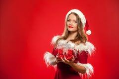 Boże Narodzenia, mas, zima, szczęścia pojęcie - uśmiechnięta kobieta w Santa pomagiera kapeluszu z prezenta pudełkiem nad czerwon Fotografia Stock