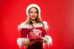 Boże Narodzenia, mas, zima, szczęścia pojęcie - uśmiechnięta kobieta w Santa pomagiera kapeluszu z prezenta pudełkiem nad czerwon Obraz Royalty Free