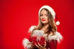 Boże Narodzenia, mas, zima, szczęścia pojęcie - uśmiechnięta kobieta w Santa pomagiera kapeluszu z prezenta pudełkiem nad czerwon Obrazy Royalty Free