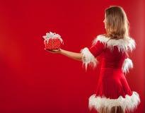 Boże Narodzenia, mas, zima, szczęścia pojęcie - uśmiechnięta kobieta w Santa pomagiera kapeluszu z prezenta pudełkiem nad czerwon Zdjęcia Royalty Free