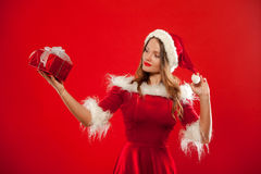 Boże Narodzenia, mas, zima, szczęścia pojęcie - uśmiechnięta kobieta w Santa pomagiera kapeluszu z prezenta pudełkiem nad czerwon Fotografia Royalty Free