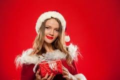 Boże Narodzenia, mas, zima, szczęścia pojęcie - uśmiechnięta kobieta w Santa pomagiera kapeluszu z prezenta pudełkiem nad czerwon Zdjęcia Stock