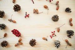 Boże Narodzenia obramiają: rożki, cynamon, jagody, acorn na drewno stole Fotografia Royalty Free