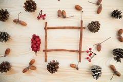 Boże Narodzenia obramiają: rożki, cynamon, jagody, acorn na drewno stole Zdjęcie Stock