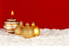 Boże Narodzenia ornamentują w śniegu na czerwonym tle obrazy stock