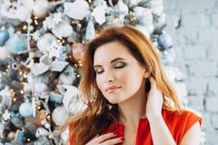 Boże Narodzenia Pięknej uśmiechniętej kobiety Elegancka nadmierna choinka w czerwieni sukni zaświeca tło szczęśliwego nowego roku obraz royalty free