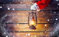 Boże Narodzenia Santa ` s ręki mienia rocznika nafciana lampa nad drewnianym tłem Obraz Royalty Free