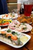Boże Narodzenia Stołu set, boczny widok Mięsa na wakacje stole Pokrojony solony śledź na białym talerzu z ziele, cytryną i oliwka Zdjęcia Stock