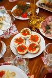 Boże Narodzenia Stołu set, boczny widok Mięsa na wakacje stole Pokrojony solony śledź na białym talerzu z ziele, cytryną i oliwka Obrazy Royalty Free