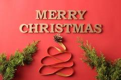 Boże Narodzenia wakacje Bożenarodzeniowy skład z dekoracyjną choinką i wpisowymi Wesoło bożymi narodzeniami na czerwonym backgrou obraz stock