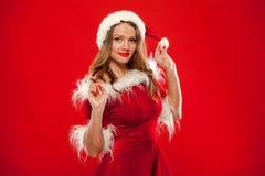 Boże Narodzenia Zamykają w górę portreta piękna seksowna dziewczyna jest ubranym Santa Claus ubrania nad czerwonym tłem, Fotografia Royalty Free