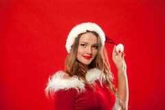 Boże Narodzenia Zamykają w górę portreta piękna seksowna dziewczyna jest ubranym Santa Claus ubrania nad czerwonym tłem, Obraz Royalty Free