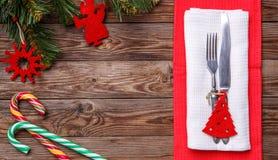Boże Narodzenia zgłaszają miejsca położenie z rozwidleniem i nóż, dekorujący boże narodzenia bawi się - czerwonej jedliny, dwa li Fotografia Stock