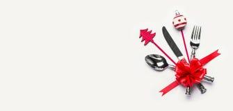 Boże Narodzenia zgłaszają położenie z cutlery, czerwonym faborkiem i minimalną dekoracją z kopii przestrzenią na białym biurka tl fotografia stock