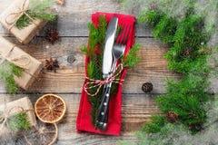 Boże Narodzenia zgłaszają położenie z talerzami, silverware, prezenta pudełkiem i dekoracjami w ciemnym drewnianym tle, szczęśliw zdjęcie stock