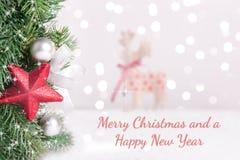 Boże Narodzenie dekorująca jodła rozgałęzia się z zamazanego tła i teksta Wesoło bożymi narodzeniami zdjęcia royalty free