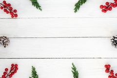Boże Narodzenie rama robić jodła liście, sosna rożki i uświęconej jagodowej dekoraci nieociosani elementy, na biały drewnianym Obrazy Stock