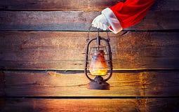 boże narodzenie w tle obramiająca wakacyjna scena Santa ` s ręki mienia rocznika nafciana lampa Zdjęcie Royalty Free