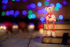 Boże Narodzenie zabawki niedźwiedź w pulowerze siedzi na książkach zdjęcie royalty free