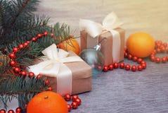 Bożego Narodzenia rzemiosła prezenta pudełka Czerwoni koraliki i jodeł gałąź Cristmas tło Tangerine i nowego roku teraźniejszość fotografia royalty free