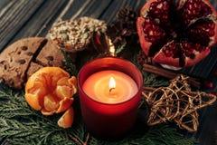 Bożenarodzeniowa świeczka i teraźniejszość z czerwonymi ciastkami faborku i garnet Obrazy Stock