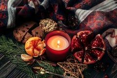 Bożenarodzeniowa świeczka i teraźniejszość z czerwonymi ciastkami faborku i garnet Zdjęcie Stock