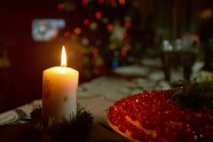 Bożenarodzeniowa świeczka na ciemnym tle przed jedliną fotografia stock