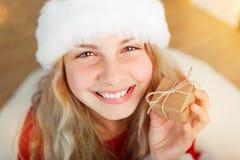 Bożenarodzeniowa czas dziewczyna przyglądająca z prezentem w jej ręce up zdjęcia stock