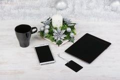 Bożenarodzeniowa dekoracja, czarny kubek i technologia przyrząda z pustymi ekranami na białym drewnianym tle, Egzamin próbny zdjęcia stock
