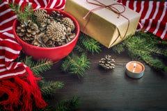 Bożenarodzeniowa dekoracja - czerwony puchar pełno rożki, prezenta pudełko zawijający w Kraft papierze, sosen gałąź, świeczka, cz Obraz Stock