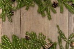 Bożenarodzeniowa dekoracja jedlinowy drzewo z sosną konusuje na drewnianym bac Obrazy Royalty Free