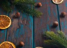 Bożenarodzeniowa dekoracja na drewnianym nieociosanym biurku Cytrusy suszący plasterki, jedlinowe gałąź i hazelnuts, zdjęcia royalty free