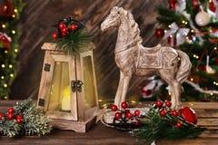Bożenarodzeniowa dekoracja z drewnianym koniem i retro świeczka lampionem zdjęcie stock