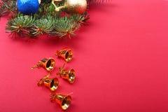 Bożenarodzeniowa dekoracja z Pięknymi złocistymi dzwonami, kolorowymi piłkami i faborkami na czerwonym tle, Zdjęcia Stock