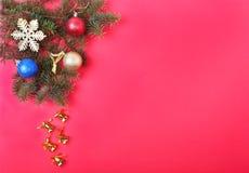 Bożenarodzeniowa dekoracja z Pięknymi złocistymi dzwonami, kolorowymi piłkami i faborkami na czerwonym tle, Fotografia Royalty Free