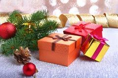 Bożenarodzeniowa dekoracja z prezentów pudełkami, kolorowymi boże narodzenie piłkami, choinką i rożkami na, rozmytym, lśnieniu, i Obraz Royalty Free