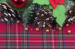 Bożenarodzeniowa dekoracja z złotych piłek naturalnymi rożkami na szkockiej kracie jak Obraz Royalty Free