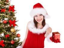 Bożenarodzeniowa dziewczyna w Santa prezenta kapeluszowym daje pudełku. Obrazy Royalty Free